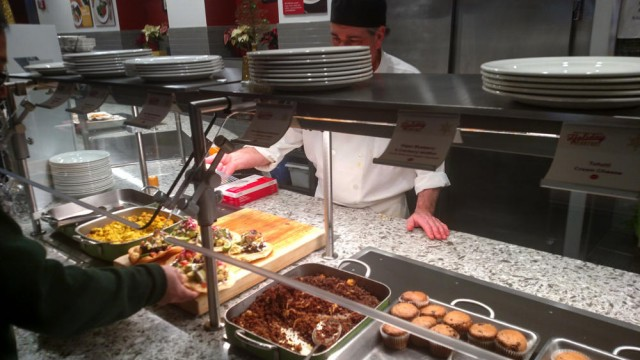 Vegan muffins, hash, bacon, and other plant-based options are served at a cafeteria counter