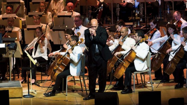 Johnson plays his harmonica with the Boston Pops orchestra behind him.