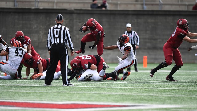 Harvard running back Aaron Shampklin hops over a Harvard teammate with a football in hand.