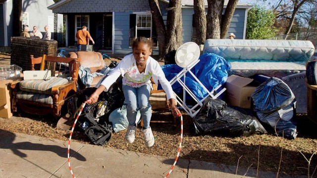 A young girl jumps rope on the sidewalk next to her family's belongings after they received a court order of eviction that was carried out by McLennan County deputy constables in Waco, Texas. Families like hers are the kind of clients badly in need of legal representation—and most often unlikely to receive it.
