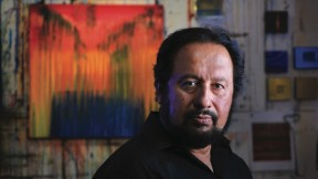 Painter George Oommen in his studio. His painting <em>Visions of Kerala 2</em> (acrylic on  canvas, 2005) hangs behind him.