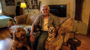 Elizabeth Thomas shown on her couch at home with her own small dogs, Chapek and Kafka, and her son's large dog, Clover, whom she watches when he is away.