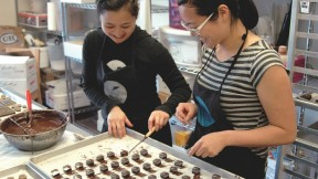 In the Sôcôla kitchen, sisters Wendy (left) and Susan Lieu dip a few dozen chocolate truffles laid out on baking parchment.