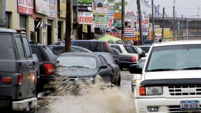 Puddles of water, a leitmotif in <i>Foreign Parts,</i> fill the rutted streets of Willets Point in Queens, a mecca for auto repair and parts.
