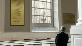 In Memorial Church, General George W. Casey Jr. views the plaque commemorating the Harvard dead of the Vietnam War, among them his father, George W. Casey '45.