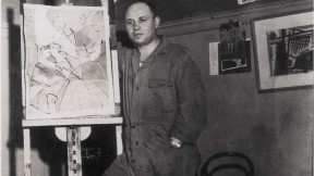 Photograph of artist Romare Bearden standing by an easel c. 1940