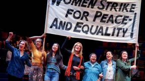 "Scene from ""Gloria, A Life,"" showing women marching in solidarity with protest sign"