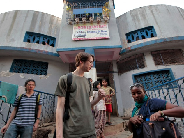 Muhammad Farid Abdul Rahman, Jimmy Potter, and Gitangu stop outside after surveying a public toilet building and interviewing the desk attendant about the bathroom's cost and cleaning schedule.