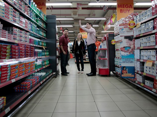 "A new required course places almost all the 900 first-year M.B.A. students in one of 10 foreign countries for a weeklong project; the largest contingent went to India. In Mumbai, one student team worked with a chain of ""hypermarkets"" trying to win business from small neighborhood grocery stores. Here, Alex Pak, Parilee Edison, and Evan Sketchley analyze store displays."