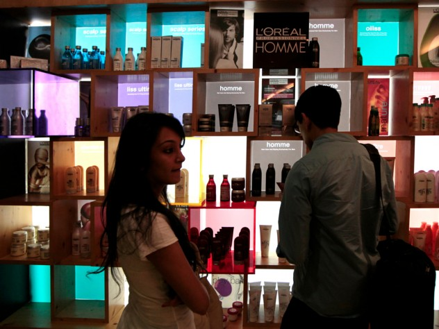 "Another group advised a company on introducing a new line of hair-care products. Here, M.B.A. student Nafis Atiqullah (right) examines a product display at a hair salon. At left is Riddhi Paleja; her aunt, the Harvard students' local guide, brought her along for the day because she thought the students might find it informative to interview her. She is, her aunt said, ""the only person I know who uses a lot of hair products."""