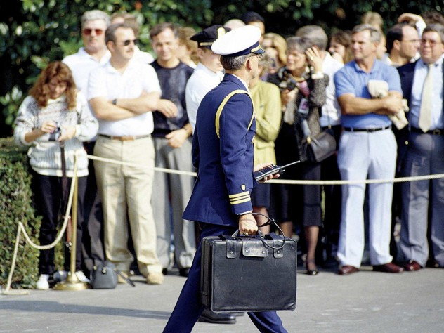 "A military aide to President George H.W. Bush carries the ""nuclear briefcase,"" cabled to his wrist, in 1991."