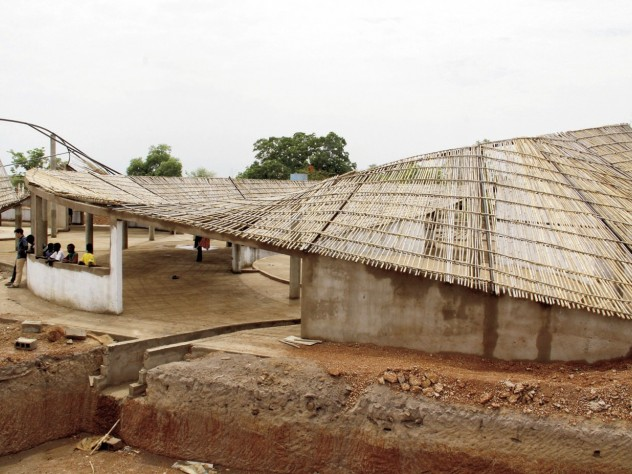 The undulating roof, constructed of local bamboo and thatch, is designed to catch rainwater for community use.