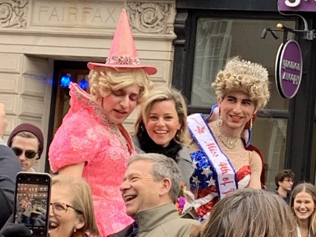 Elizabeth Banks looks at the camera as she rides in a convertible with two members of the Hasty Pudding Theatricals.