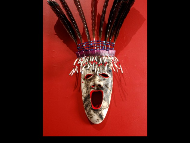 """The <em>Arctic Dancer</em> mask demonstrates Charette's """"horsehair firing"""" technique, which entails heating clay to 1,800 degrees Fahrenheit and dropping individual hairs onto it to produce a streaked effect. White """"stars"""" around one eye represent a connection to the spirit world; below the other eye is a mole. Yup'ik lore holds that people with a mole near the eye are endowed with spiritual vision; Charette has a mole in the same spot, and uses the mark in his art as a signature."""