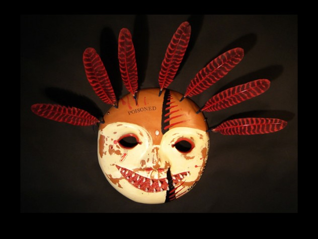 """Charette traveled to the Smithsonian Institution in 2003 to view the museum's Yup'ik holdings; the mask above, from his Poisoned series, shows that trip's influence and comments on the way museums handled Native American art objects, many of which have sacred value. Charette saw many Yup'ik masks that had been treated with arsenic as a pesticide when the museum acquired them, then further defiled by stamping them with the word """"poisoned"""" once the dangers of topical exposure to arsenic became known."""