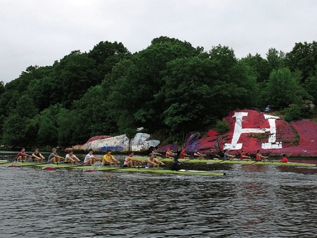 "Two Harvard crews (right) row past ""The rock,"" long contested as a site for Harvard or Yale partisan artwork."