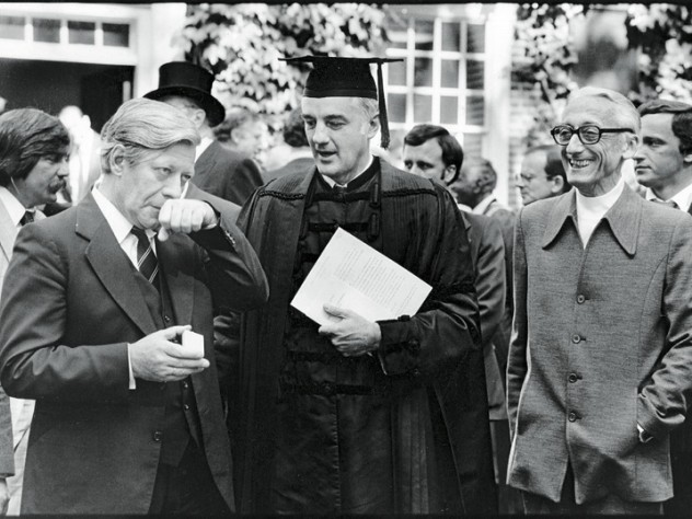 President Derek Bok and honorand Jacques-Yves Cousteau observe West Germany's chancellor, honorand Helmut Schmidt, pause for a pinch of snuff (1979).