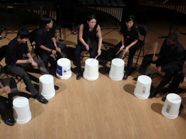 The ensemble's trademark is using offbeat objects, such as stools and buckets, as well as traditional percussion instruments.