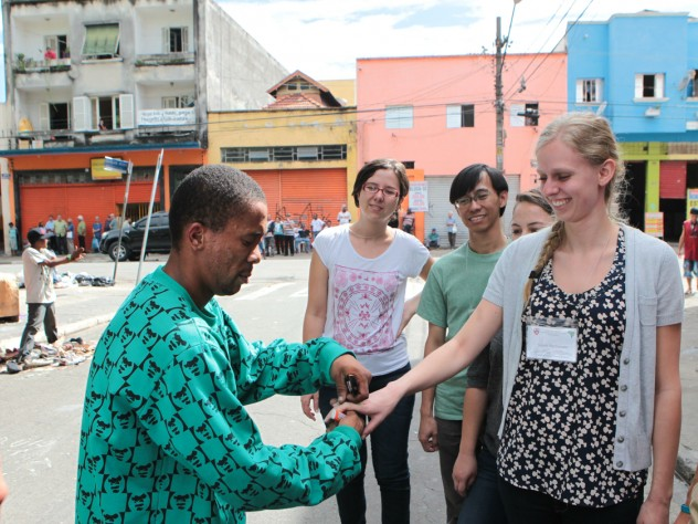 During a tour of a shantytown in the heart of São Paulo, a resident feigns a wedding proposal to HSPH's Sarah MacDonald, as University of São Paulo's Ana Carolina Navarrete (left) and HSPH's Panji Hadisoemarto look on.