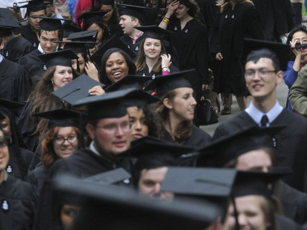 After a traditional doffing of caps to John Harvard, seniors process to Memorial Church.