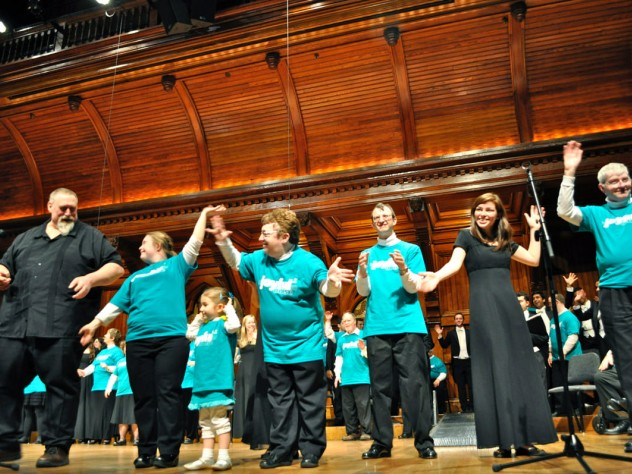"Local composer Nick Page (at left), conductor of the Mystic Chorale, takes a bow with chorus and Collegium Musicum members after they performed his song ""Do You Shine"" (written especially for Joyful Noise) as an encore. Sharing the applause is Katie Fromm, daughter of the chorus's co-founder and conductor, Allison Fromm."