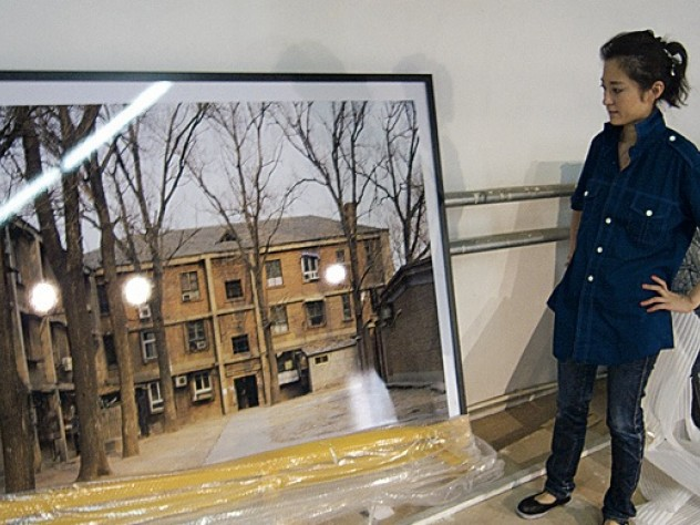 Graduate  student Ren Wei with one of Wang Di's photographs  at a studio in Beijing.