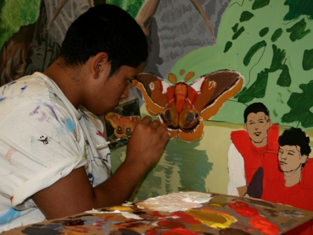 Student painting a section of <i>Mystic River Mural</i>