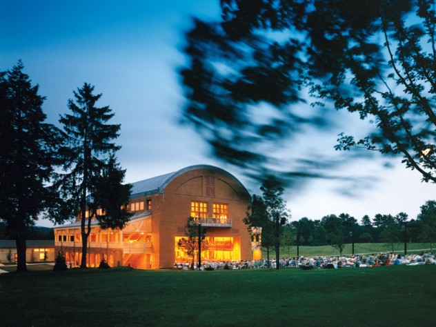 "Seiji Ozawa Hall at Tanglewood, the summer home of the Boston Symphony Orchestra, in Lenox, Massachusetts. The hall opened in 1994. With the ""barn door"" open, picnickers enjoy a concert."