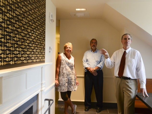 Architect Stephen Kieran (at right), Quincy co-master Deborah Gehrke, and Harvard's senior director of project management Steve Needham, point out that on upper floors, in a gesture to returning alumni, a graphic designer mounted old room keys (now replaced with electronic cards for access to entryways, floors, and rooms) in eight different patterns; they are hung over fireplaces.