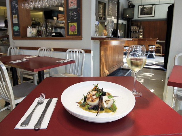 Strip T's nuanced fare, such as these sea scallops with yellow curry and chanterelles, is served in simple environs.