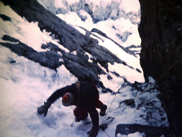Peter Carman climbing a steep rock and ice gully above Camp One