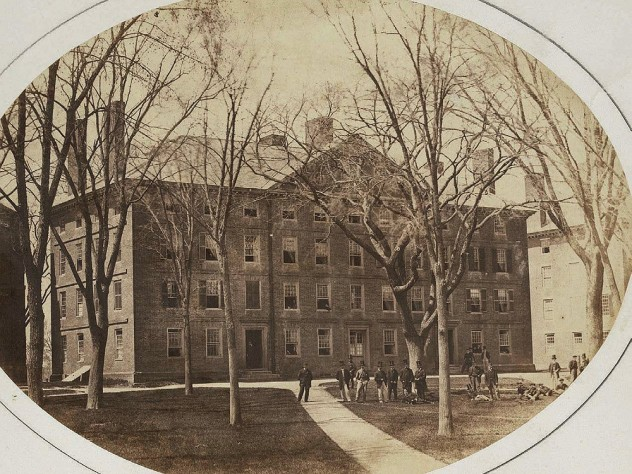 "Old photograph of Hollis Hall with students gathered around the large ""Rebellion Tree"" in front of the building."