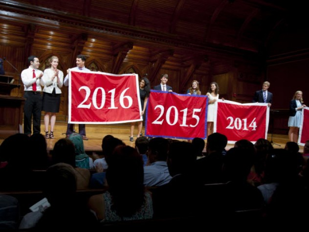 Harvard Alumni Association president Carl Muller '73, J.D.-M.B.A. '76 (at left), presents the Class of 2016 with its official banner during the Sanders Theatre portion of Freshman Convocation.