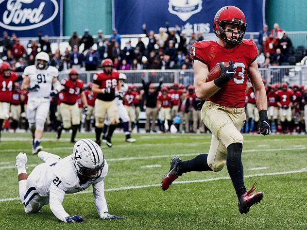 Harvard wideout Jack Cook, on his way to the end zone, runs by an outstretched Yale defender