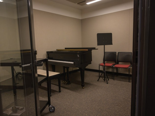 A music practice room with a piano and music stand