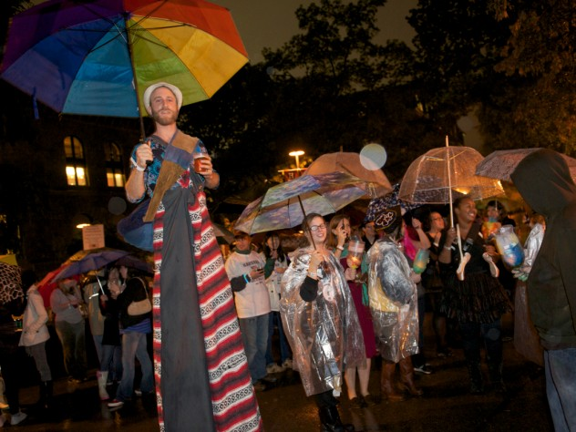 "The Divinity School parade had a ""pilgrimage"" theme and was led by a colorful stilt walker."