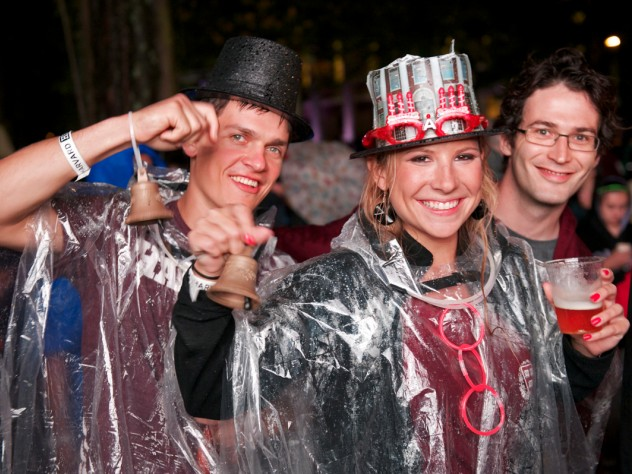 Students from the Harvard Business School (HBS) party on despite the rain. The HBS contingent in the parade carried replicas of the centennial bell from that school's 2008 anniversary.