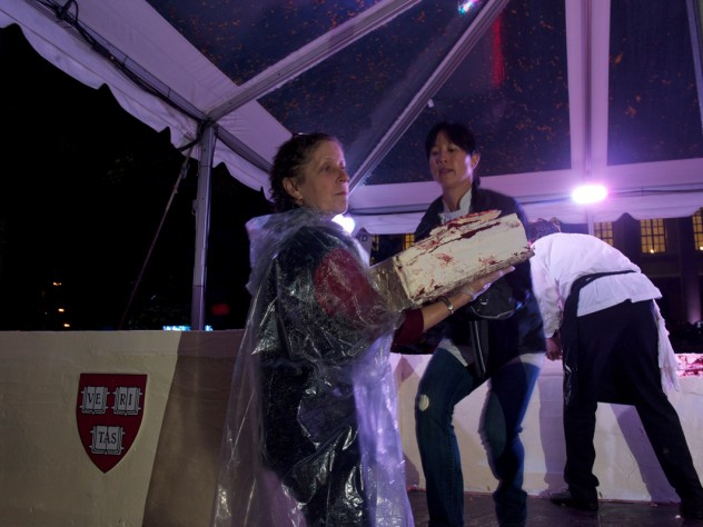 The moment the crowd has been waiting for: Joanne Chang '91 begins to remove layered sheets from her massive red velvet cake so pieces can be cut and served.