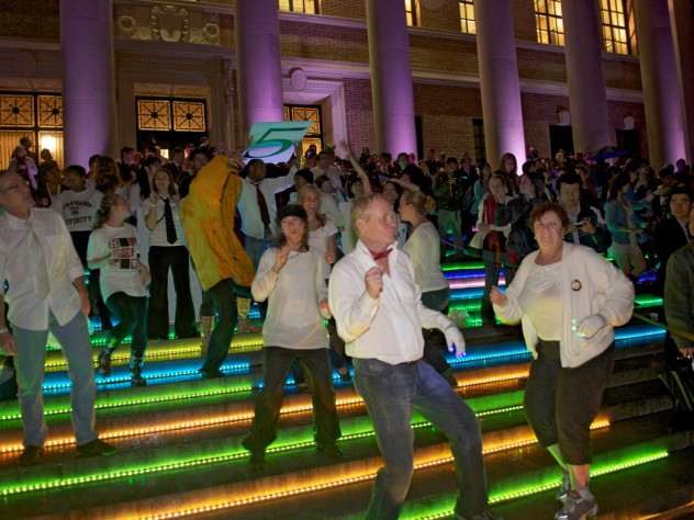 "To get the evening's dancing started, a ""flash mob"" of dancers performed a choreographed routine they'd rehearsed throughout the previous week. The dancers were on the steps of Widener Library and at other Yard locations. Colorful LED lighting decorated buildings around the Yard."