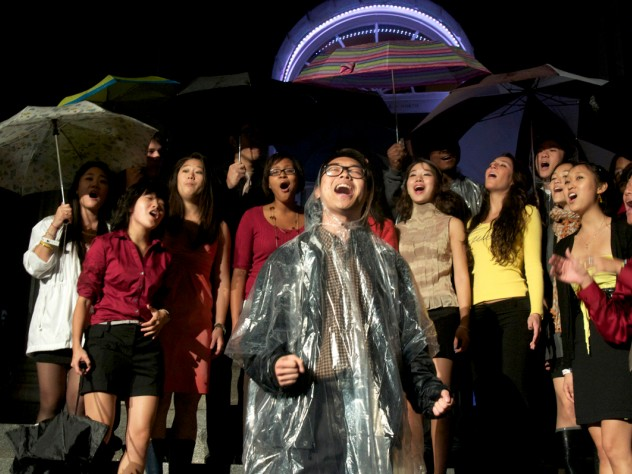 An a cappella group performs in the rain. Despite monsoon-like weather, dozens of student music and dance groups performed in Harvard Yard as part of the evening's program.