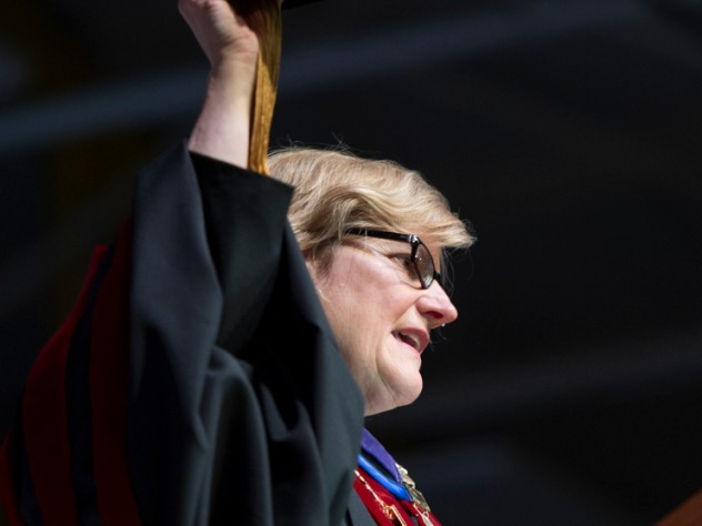 Clayton Spencer hoists the cap that her father, Samuel Reid Spencer, wore as president of Mary Baldwin College and of Davidson College, during her installation ceremony as the eighth president of Bates College.