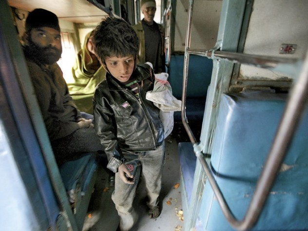 At the train station in Jaipur, India, collecting empty water bottles fetches about 100 rupees ($2) a day. Here, eight-year-old Badal searches inside a train car.