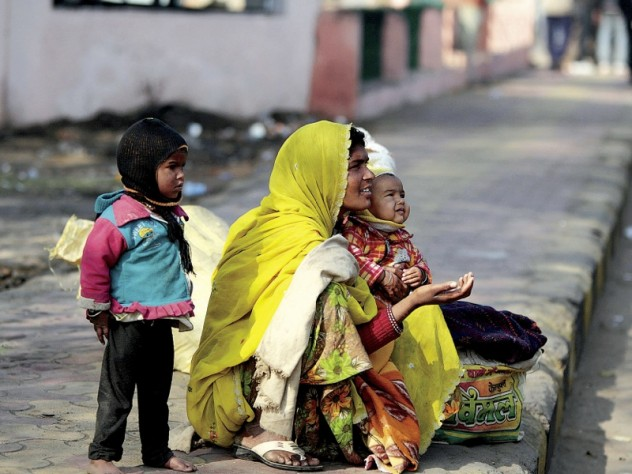 Families make their homes on a sidewalk adjacent to the train station, and survive by begging.
