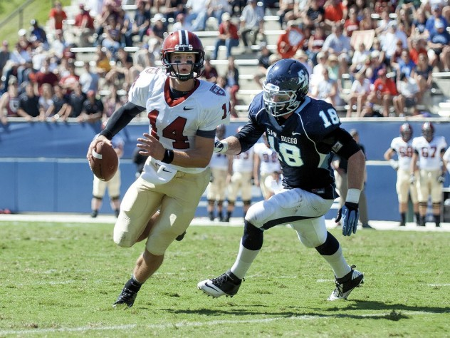 Conner Hempel (14), making his first start at quarterback, threw four touchdown passes as Harvard opened the season with a victory over the University of San Diego. The pursuing defender is end Blake Oliaro.