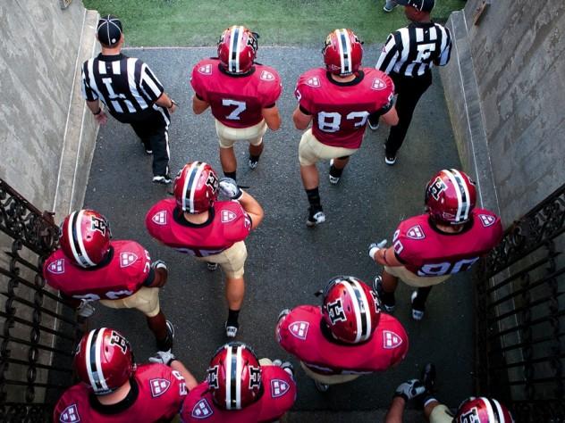 Photo of Harvard football players heading onto the field