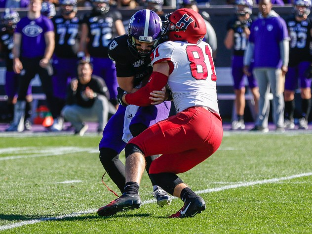 Brogan McPartland tackles Holy Cross quarterback Connor Degenhardt for a loss.