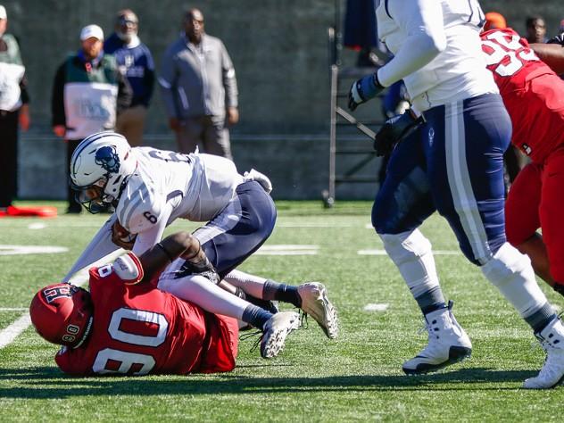 Harvard's Truman Jones drags down Howard quarterback Quinton Williams.