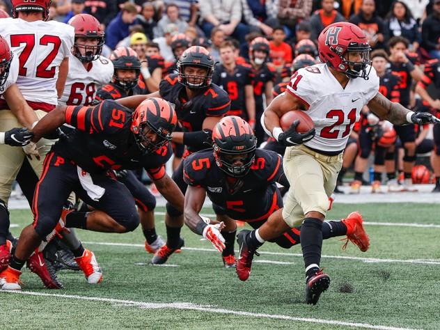 Aidan Borguet of Harvard runs by Princeton's Samuel Wright and Jeremiah Tyler.