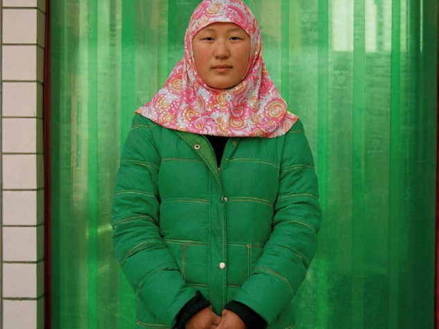 Photograph of a woman in a bright red-and-white hijab and bright green winter coat against a green curtain background, looking directly at the camera
