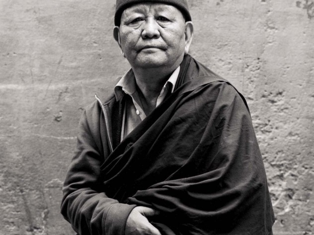 Black-and-white photograph of an older man with a robe draped over one shoulder and a zip-up sweatshirt poking out on the other, and a knit cap with a Nike logo, looks straight at the camera.